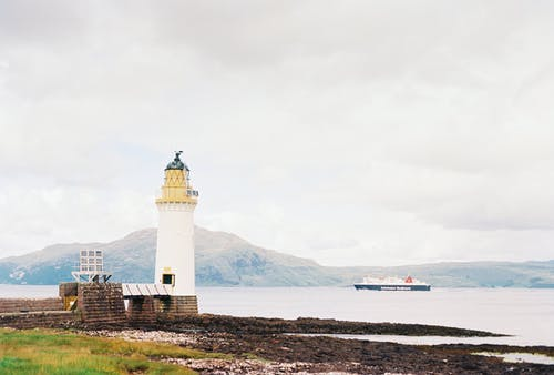 White Lighthouse Near Body of Water Viewing Mountain Under White Sky