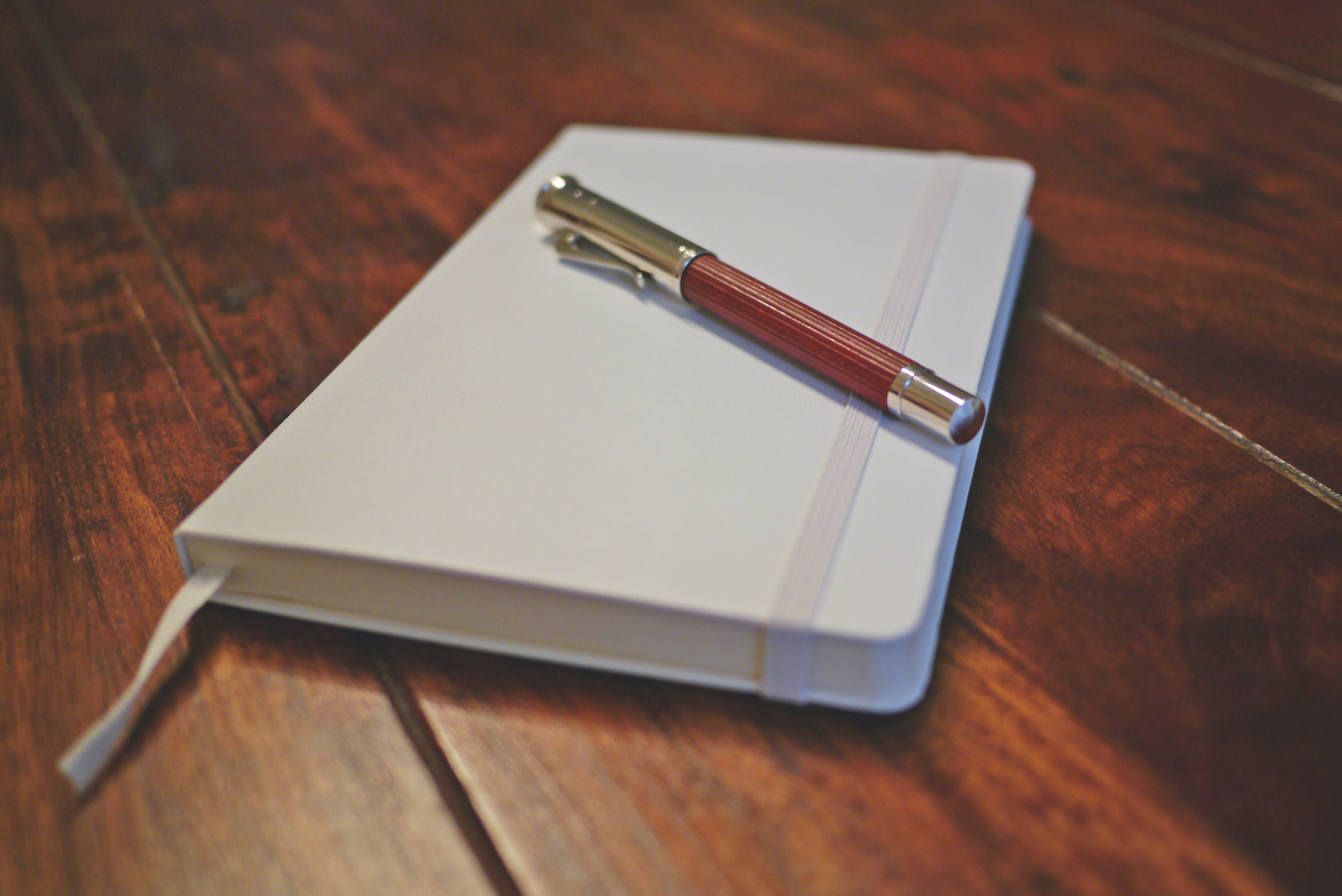 Gratis lagerfoto af fyldepen, kontorartikler, notesbog, pen