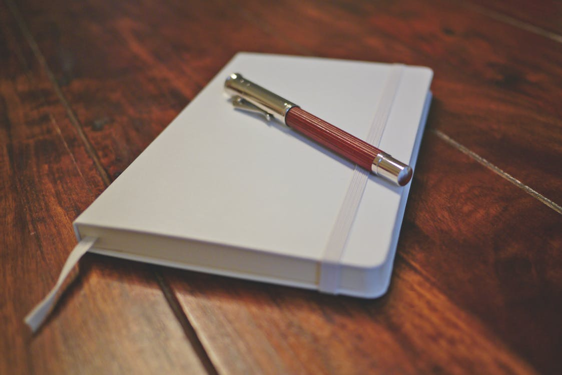 Brown Pen on White Notebook
