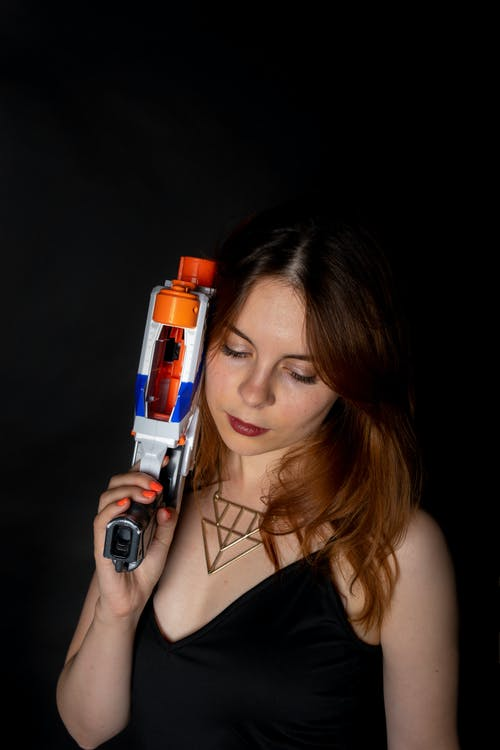 Woman Holding a Colorful Nerf Gun