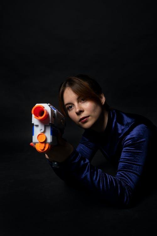 Foto d'estoc gratuïta de adult, dona, morena, pistola de joguina