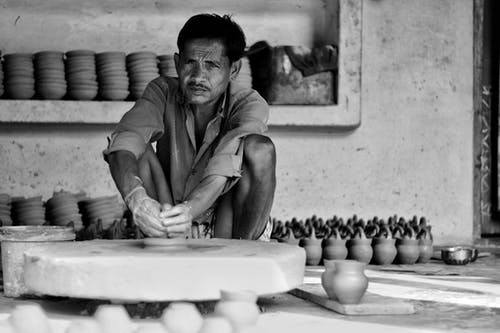 Grayscale Photography of Man Sitting Near Clay Pots