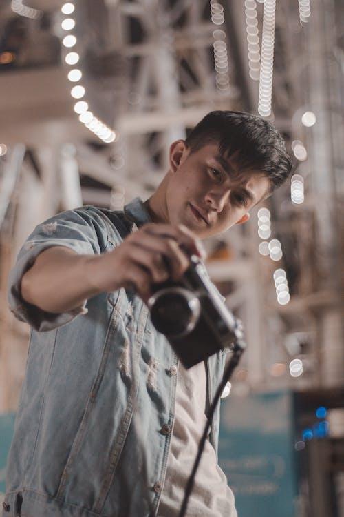 Gratis lagerfoto af brun, film kamera, fyr holder et kamera, kamera