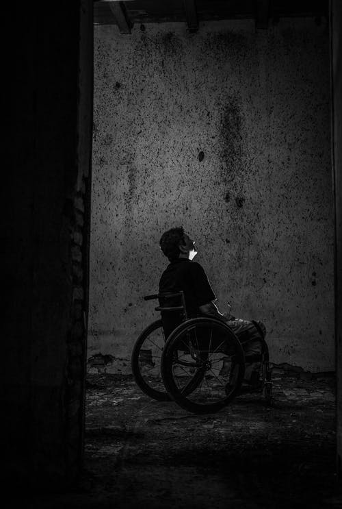 Gray scale Photo of Man Sitting on Wheelchair