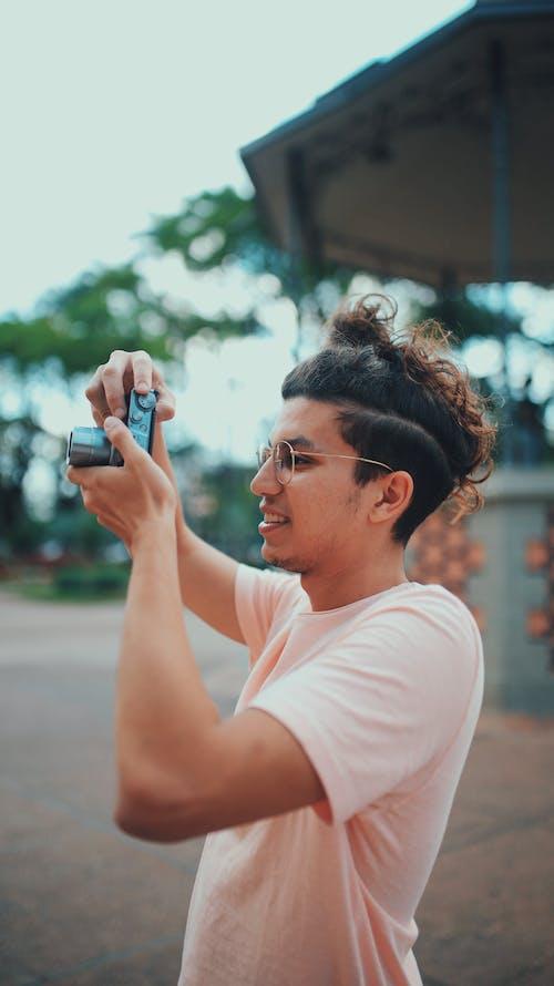 Man Wearing Pink Top Holding Camera