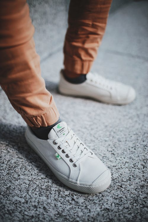 White Low Top Sneakers And Brown Pants