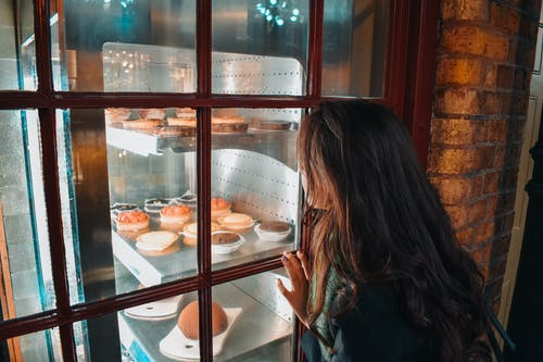 Girl Watching on Assorted Baked Pastries Beside Window Pane