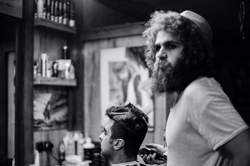 Grayscale Photography of Man Cutting Hair on Seated Man