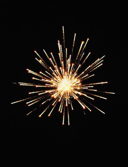 Bright golden firework bursting in dark sky at night during holiday celebration in city