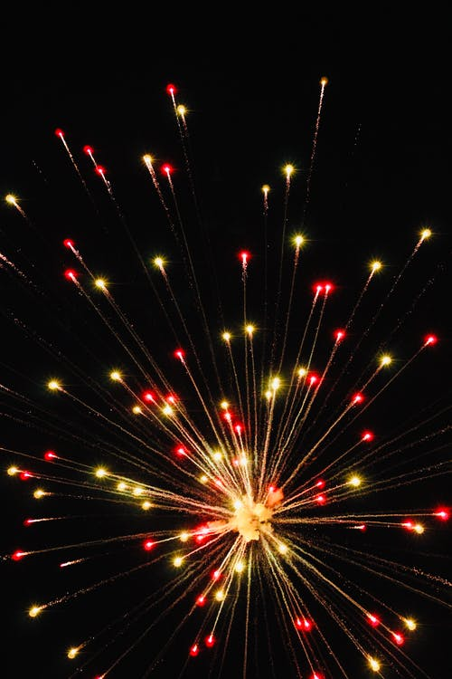 Red and yellow firework sparking in dark night sky during holiday celebration in city