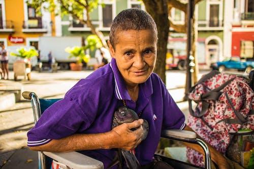 Woman Wears Purple Polo Shirt Sitting on Wheelchair