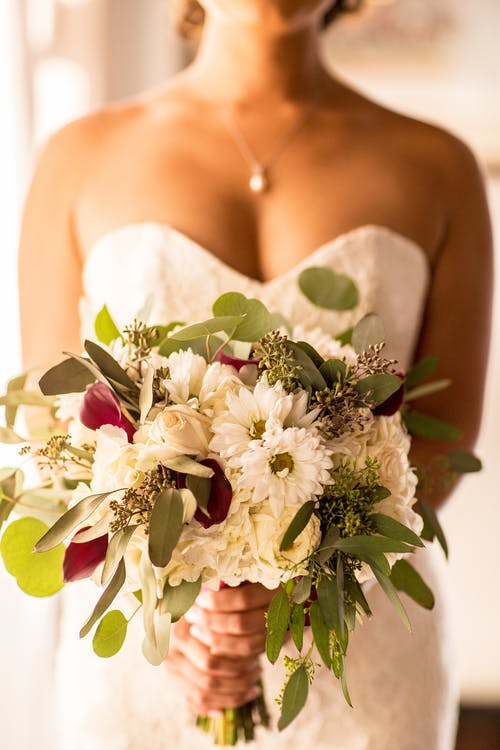 Woman Wearing White Strapless Dress Holding Bouquet Flower