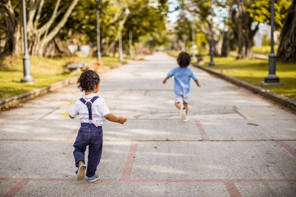 Two Children Running on Road