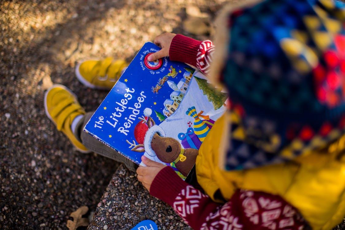 A Kid Holding  Littlest Reindeer Book
