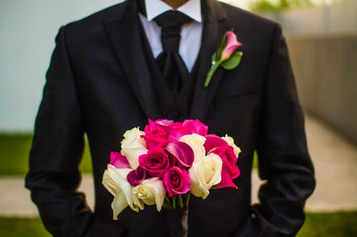Man Wearing Black Suit With A Corsage Holding Bouquet Of Flowers