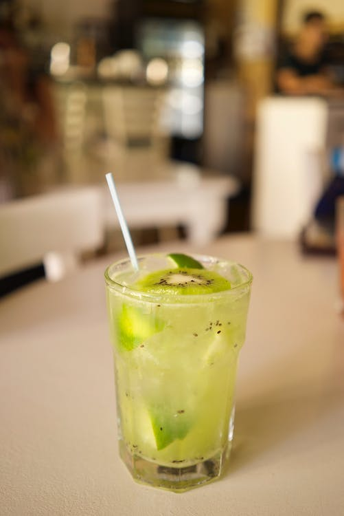 A Glass Filled With Refreshing Juice Drink With Lime And Kiwi