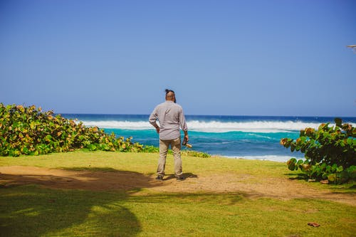 Man in Gray Top and Pants Facing Ocean