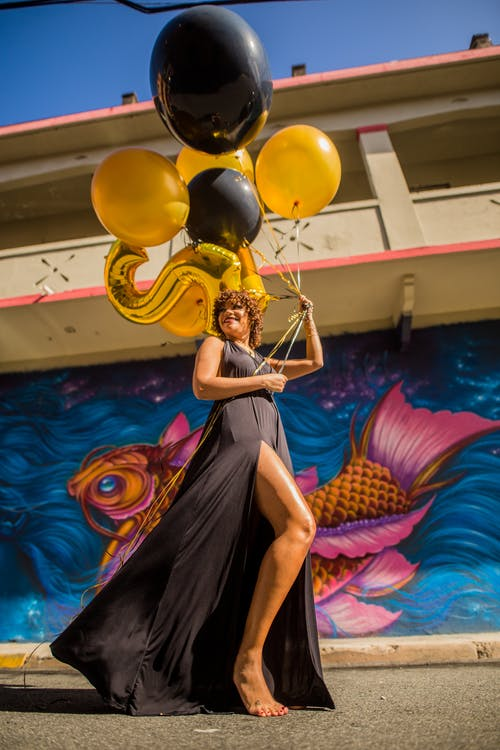 Woman in Black Dress Holding Black and Yellow Balloons