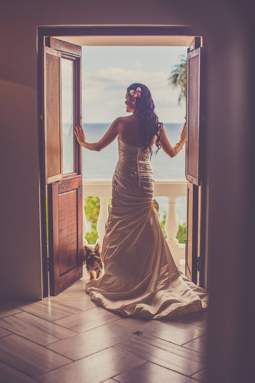 Back View Of A Woman In A Wedding Gown Standing On The Doorway Leading To A Balcony
