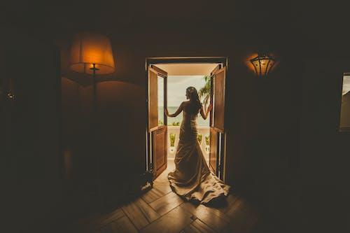 Vista Posterior De Una Mujer Vestida De Pie En La Puerta Que Conduce A Un Balcón