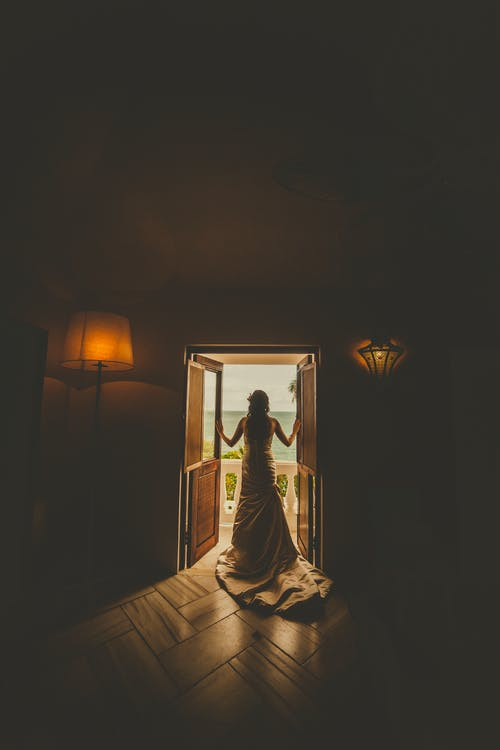 Back View Photo of Woman in Wedding Dress Standing By Doorway