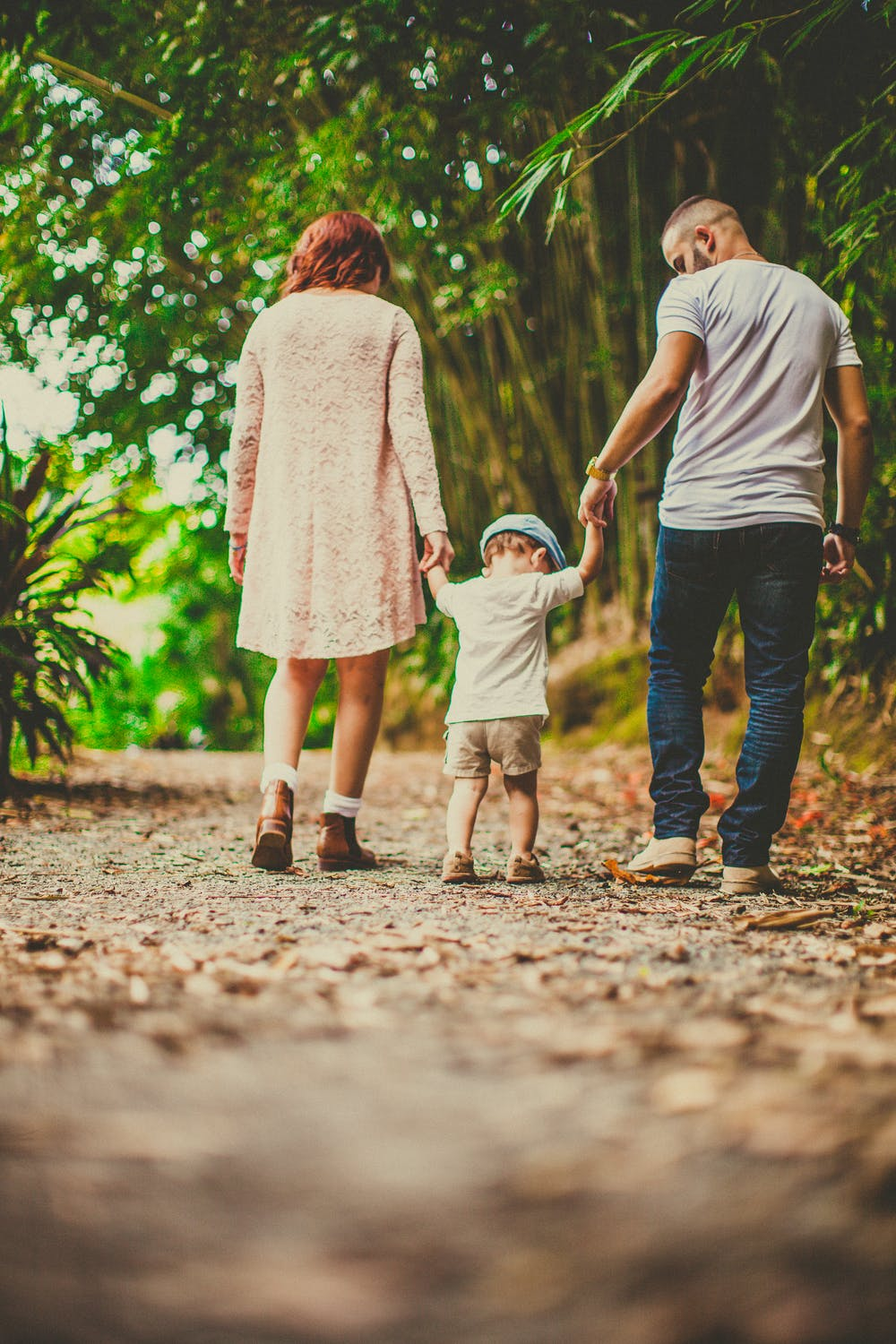 A child held by his parents on each hand while walking outdoors. | Photo: Pexels