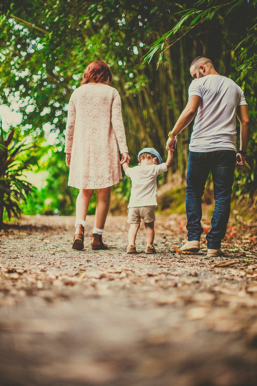 Ein Kind, das beim Spaziergang im Freien von seinen Eltern an jeder Hand gehalten wird. | Quelle: Pexels