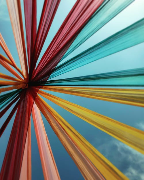 Low Angle Shot Of A Of Multi Colored Textile Attached Together On A Pole