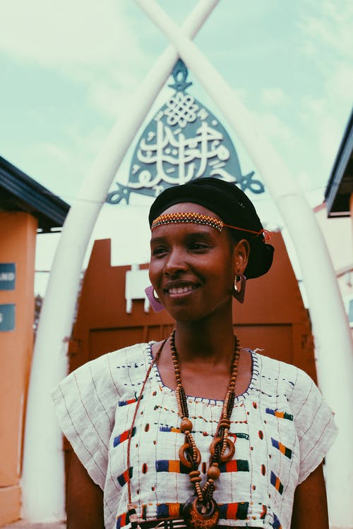 Photo of Smiling Woman in Traditional African Wear Posing While Looking Away