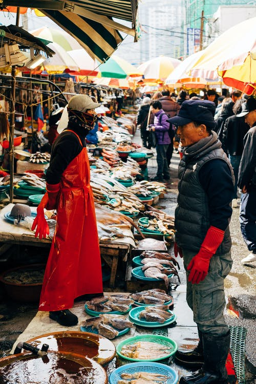 A Crowd Of People In The Fish Market Lined With Colorful Umbrellas