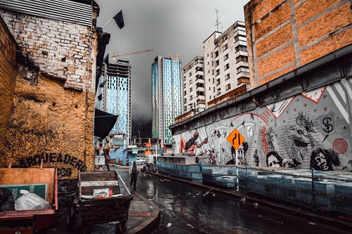 Person Walking On A Wet Street Along A Building With Mural Under Gray Sky
