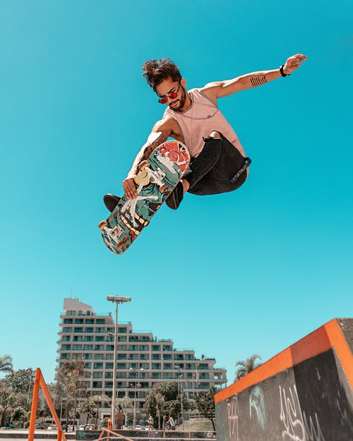 Low Angle Shot Of A Man On A Skateboard in Mid Air