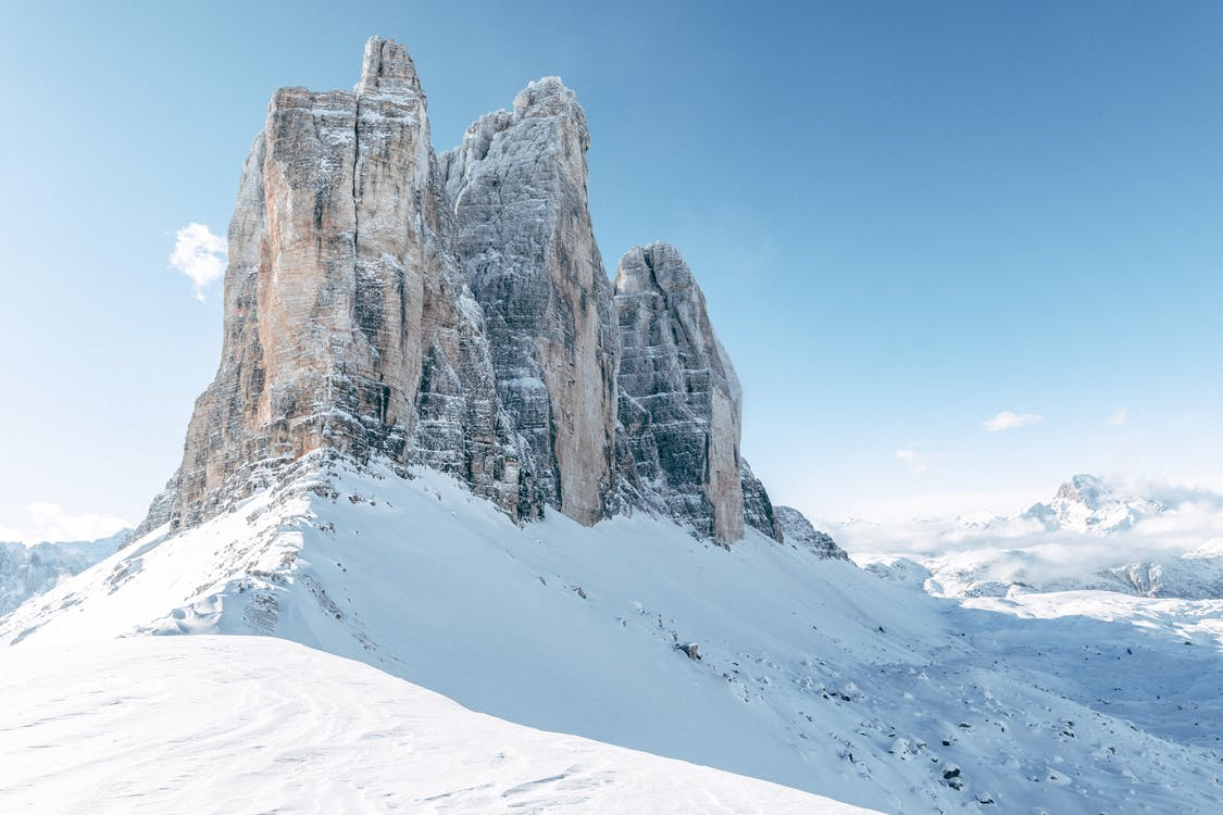 A Rock Mountain Surrounded By Snow Covered Ground
