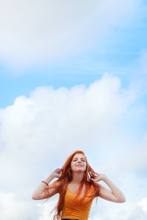 Low Angle Shot Of A Woman With Long Red Hair in Orange Scoop-neck Tank Top