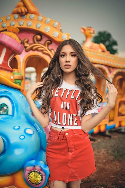 Young Woman With Long Hair In Casual Wear Standing Beside An Amusement Park Train Ride