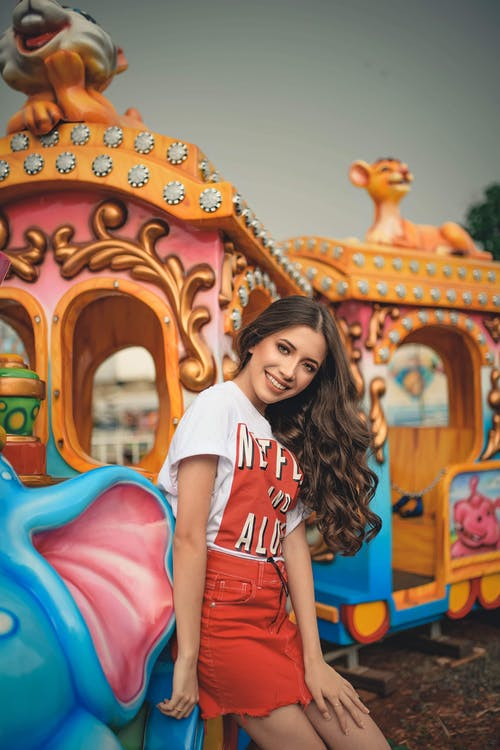 Photo of Smiling Woman in White Shirt and Red Skirt Posing by Train Ride