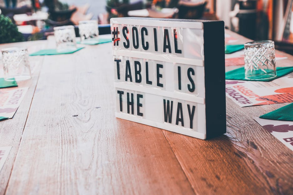 White and black signage on top of a wooden table