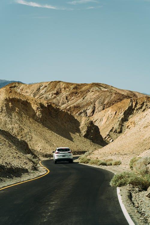 White Car on Road Between Rocks