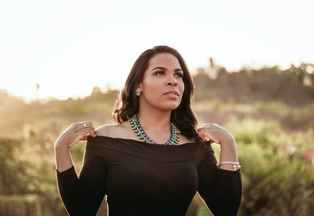 Portrait Photo of Woman in Black Off-shoulder Top Posing While Looking Away