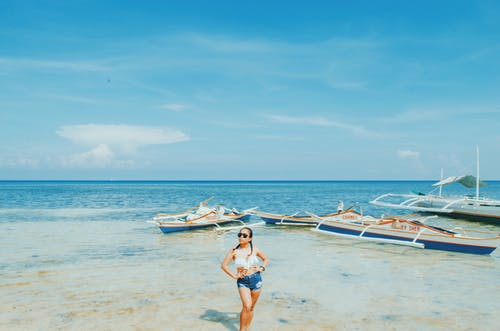 Woman Wearing White Bikini Top and Blue Short Shorts Standing Withe Both Arms Akimbo Near Sea Under Blue and White Sky