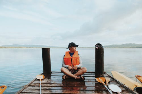 Man Wearing Life Vest While Sitting On The Dock