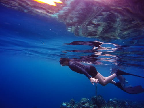 Woman In Scuba Gear Swimming Under Water Close To Suface