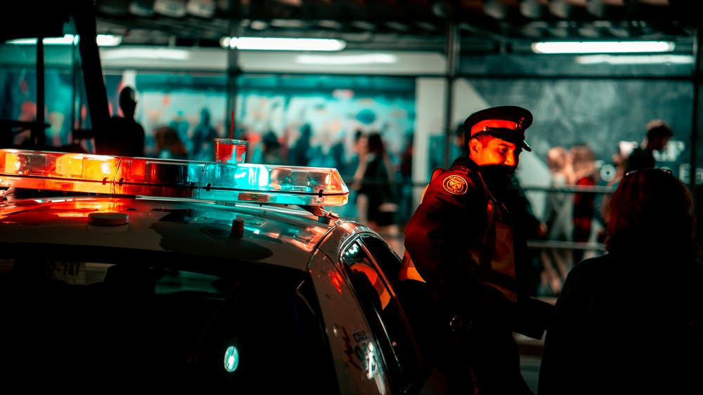 Police standing beside the police car.   Photo: Pexels