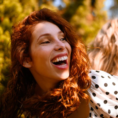 Close-up Photo of Laughing Woman in White and Black Polka-dot Top