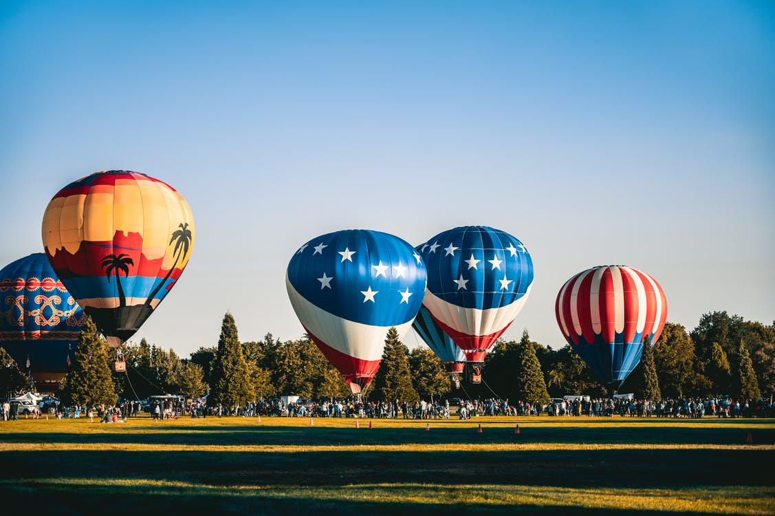 Anchored Hot Air Balloons at Field Full Of People