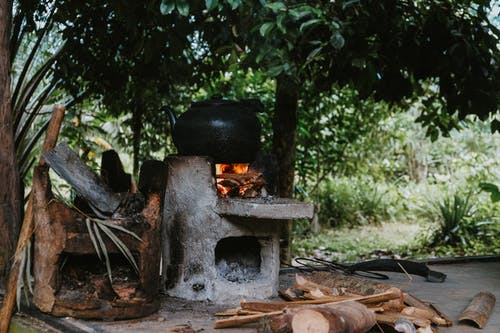 Cooking On A Black Pot Using Firewood