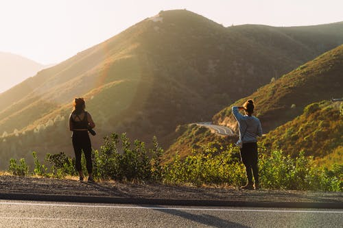 Two Women Standing Near Road Looking At Mountain