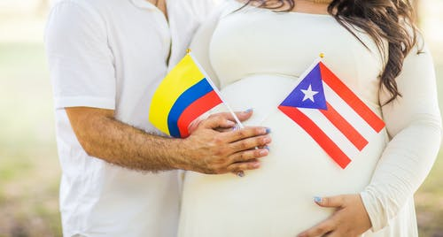 Pregnant Woman And Husband Holding Flaglets