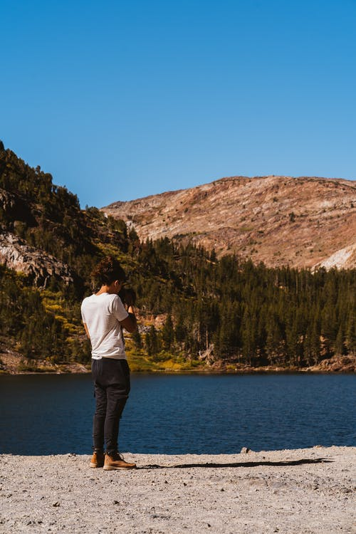 Person Talking A Photo Of The Lake Surrounded By idyllic scenery
