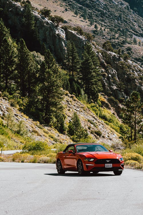 Red Ford Mustang Coupe On The Road  By The Mountains